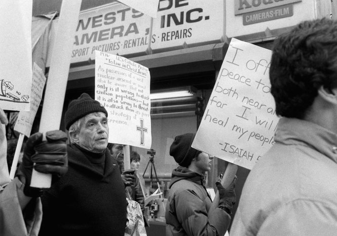 This April 9, 1982, file photo shows Daniel Berrigan, a Roman Catholic priest and Vietnam war protester, marching with about 40 others outside of the Riverside Research Center in New York. AP phot